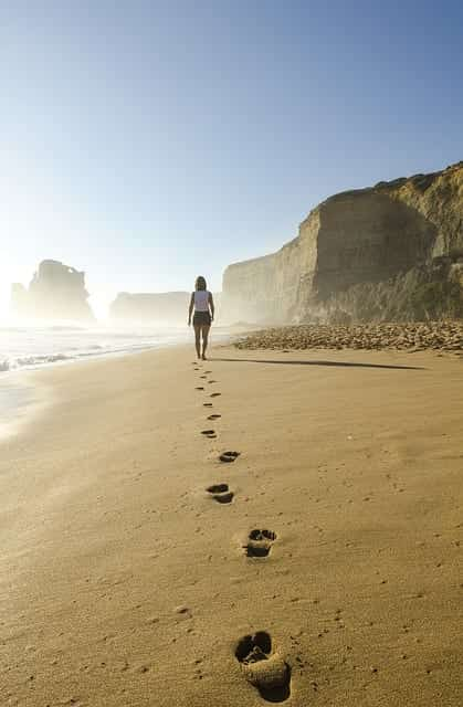 Woman in shorts and t-shirt walking along beach leaving footprints in the sand; image by Free Photos, via Pixabay.com.