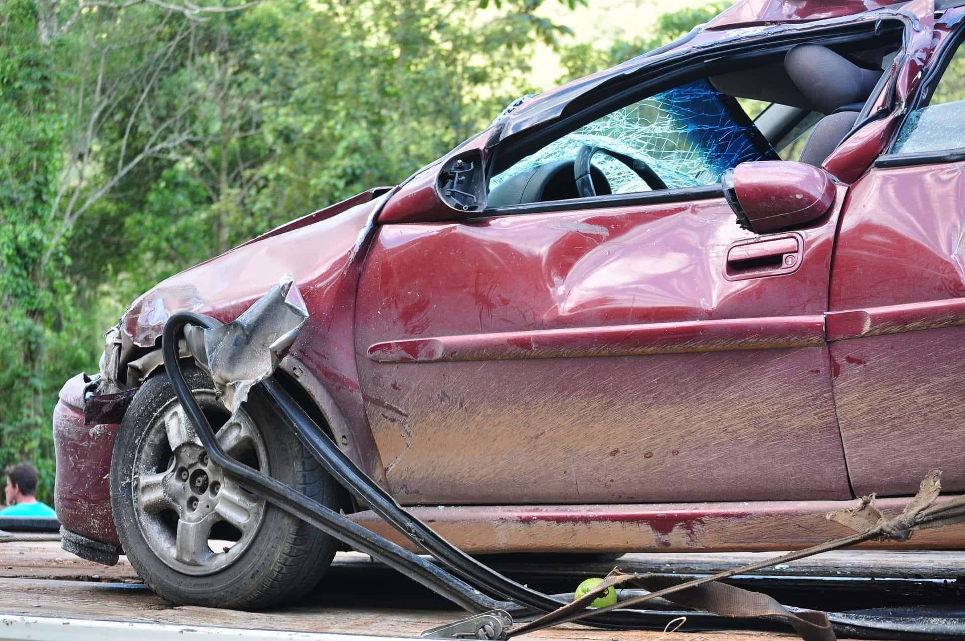 Maroon car with front-end and side collision damage; image by NettoFigueiredo, via pixabay.com.