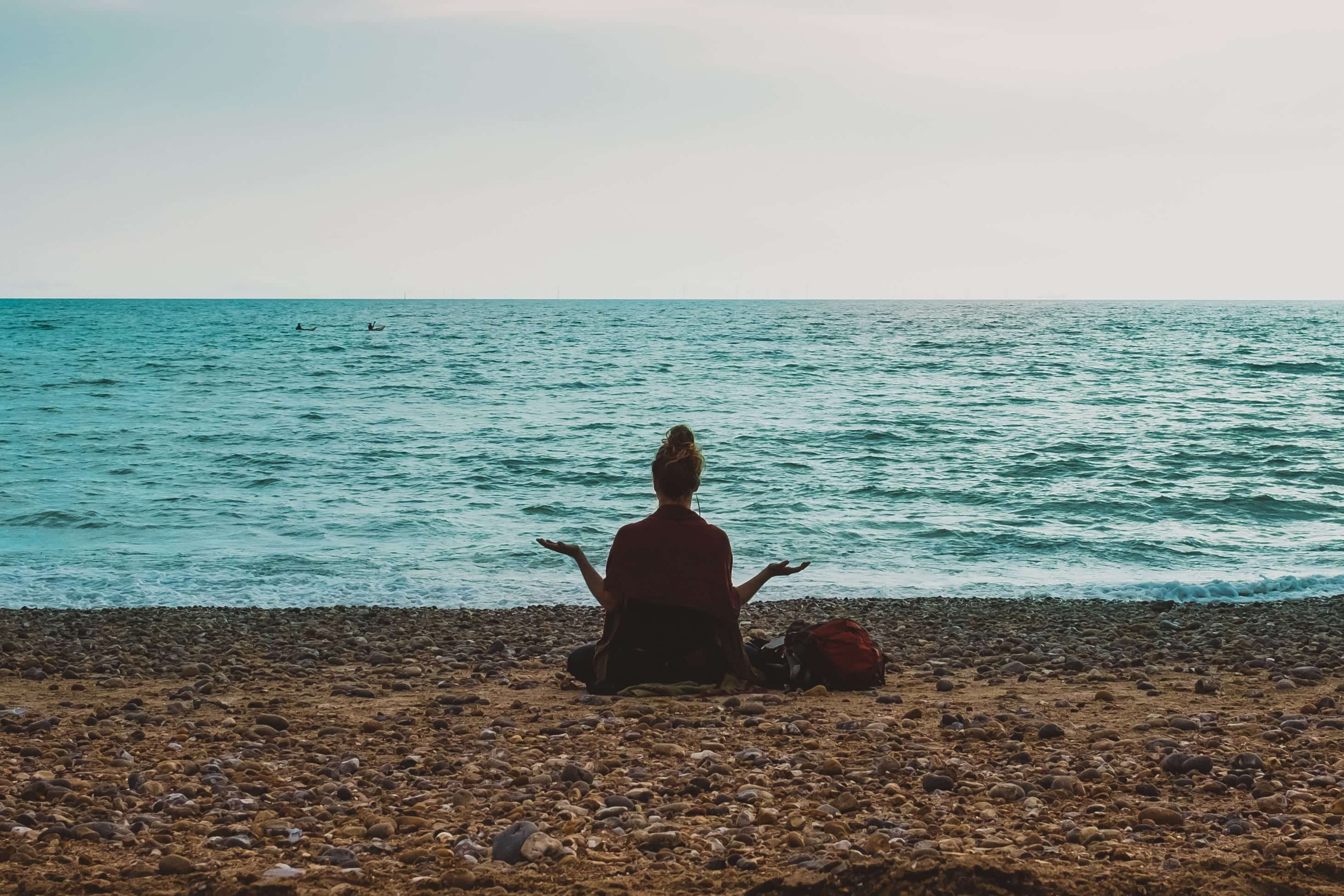 Woman meditating by a lakeshore; image by Dardan, via unsplash.com.