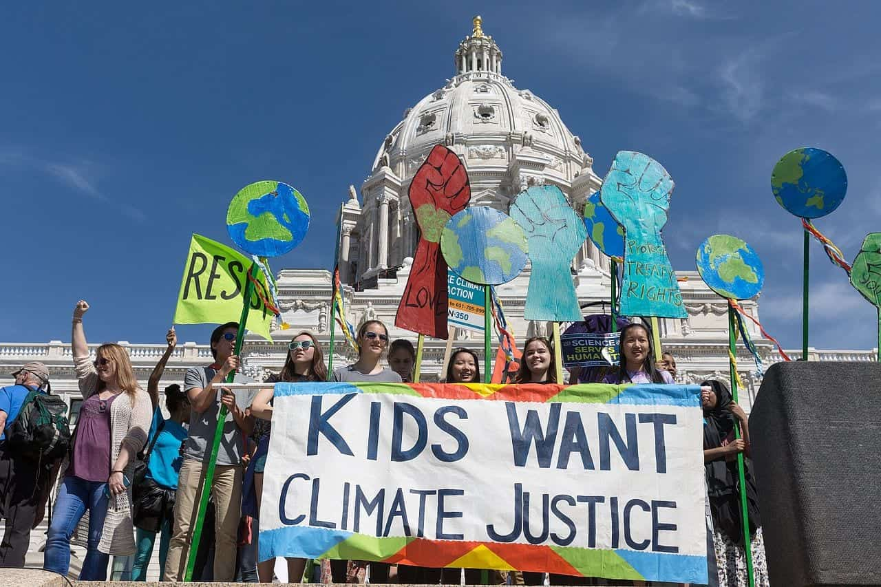 "Young people holding protest signs and a banner reading ""Kids Want Climate Justice"" in front of of a domed building on a clear day."