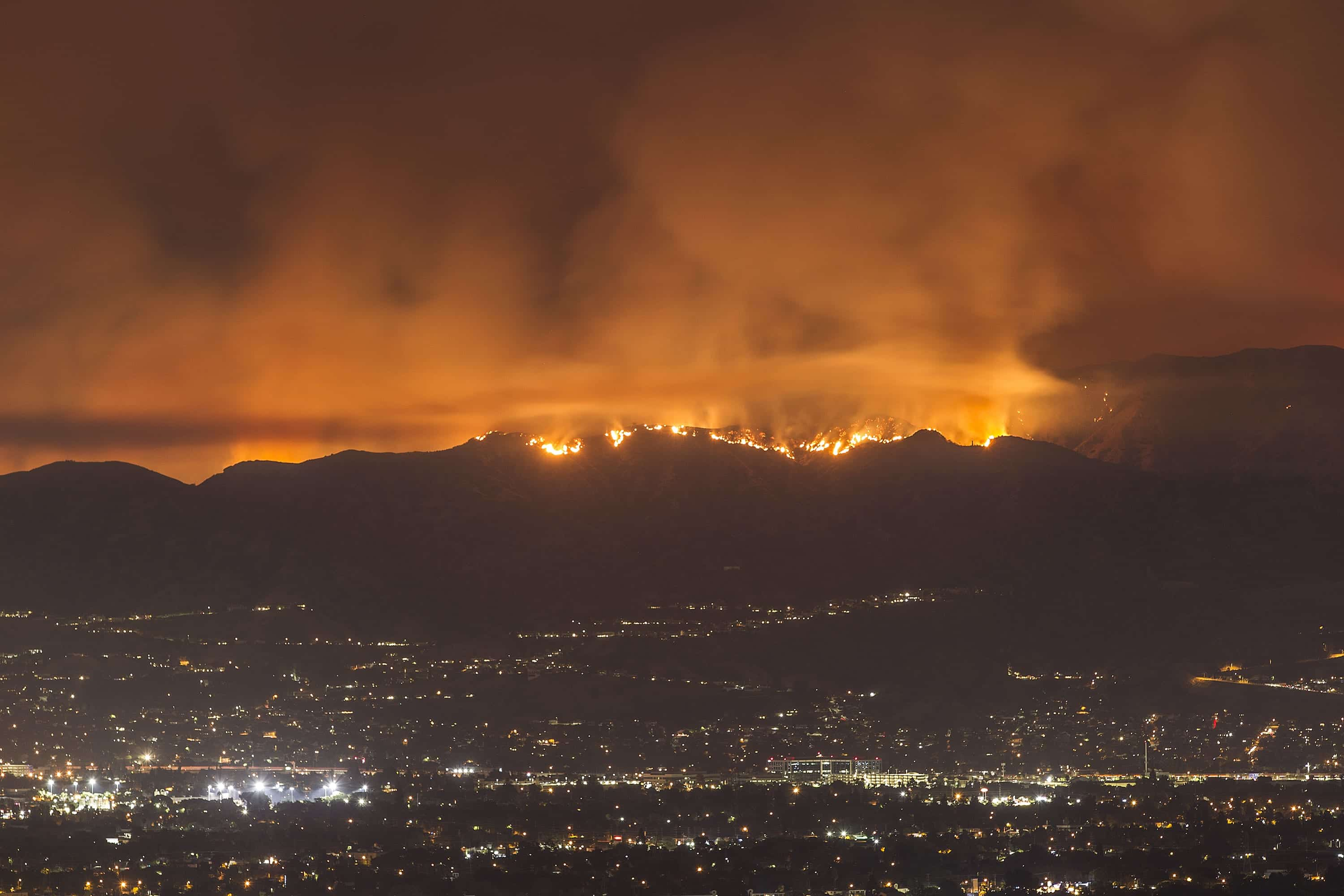 A night scene of the La Tuna fire burning in the mountains around Los Angeles. In the foreground, the city's lights shine.