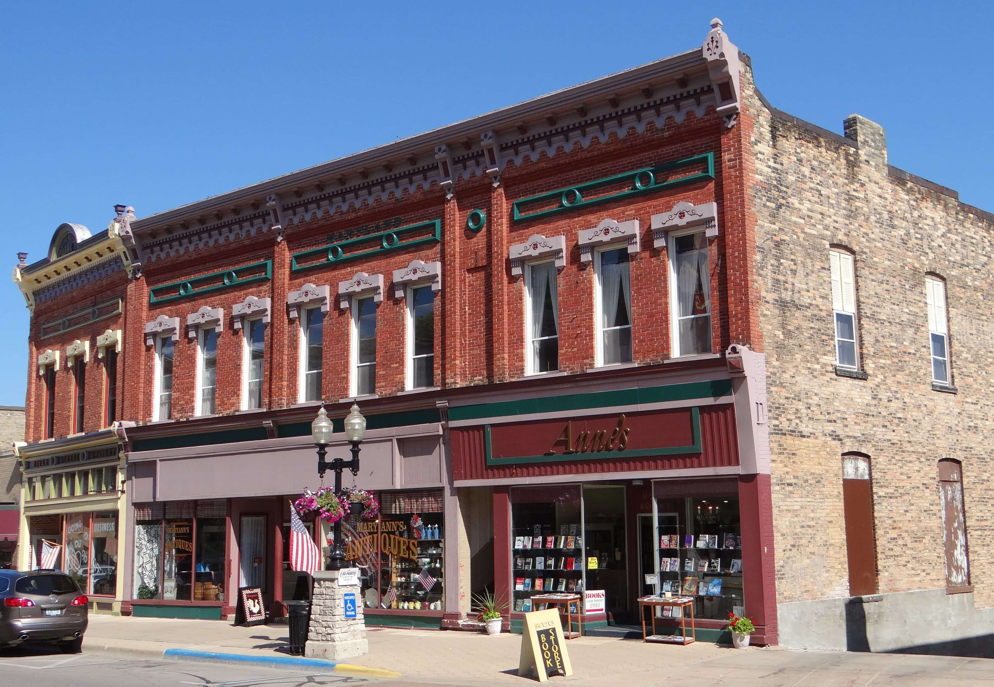 A row of two-story brick storefronts with a historic, small-town look.