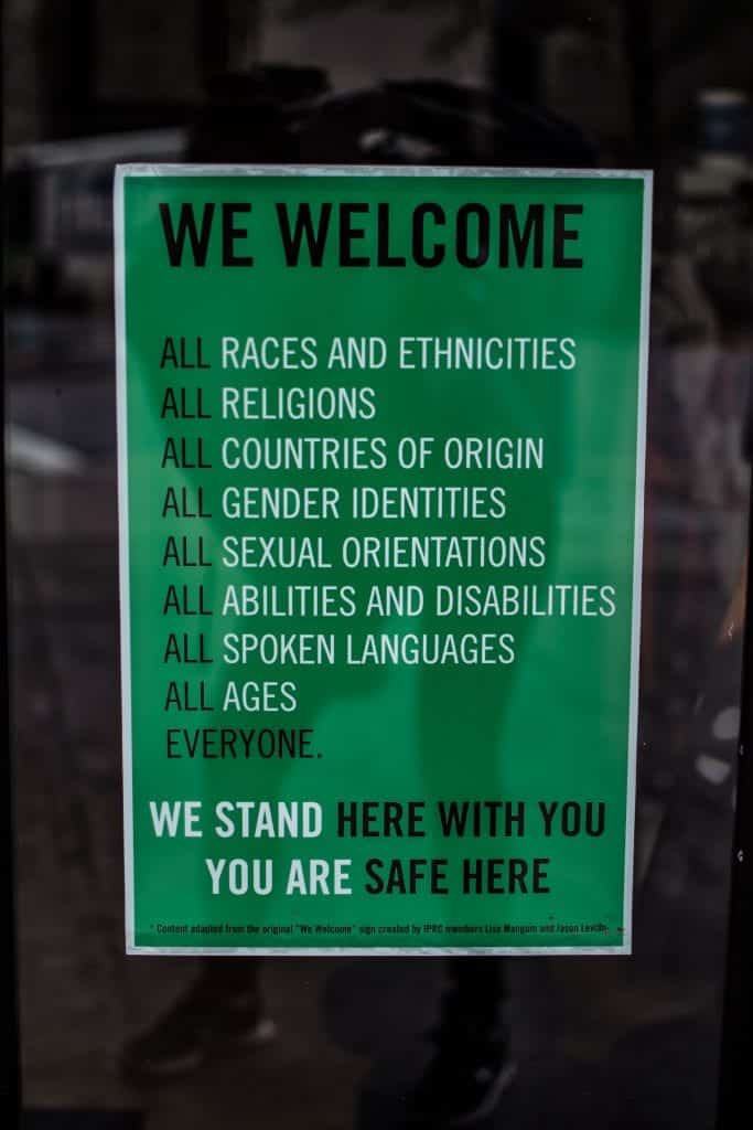 "Green sign with white lettering that reads ""We welcome all races, ethnicities, religions, countries of origin, gender identities, sexual orientations, abilities and disabilities, spoken languages, ages, everyone. We stand here with you. You are safe here."" Image by Brittani Burns, via unsplash.com."
