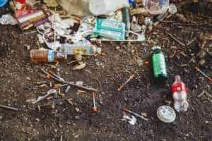 Used syringes, soda bottles, and assorted trash; image by Jonathan Gonzalez, via Unsplash.com.