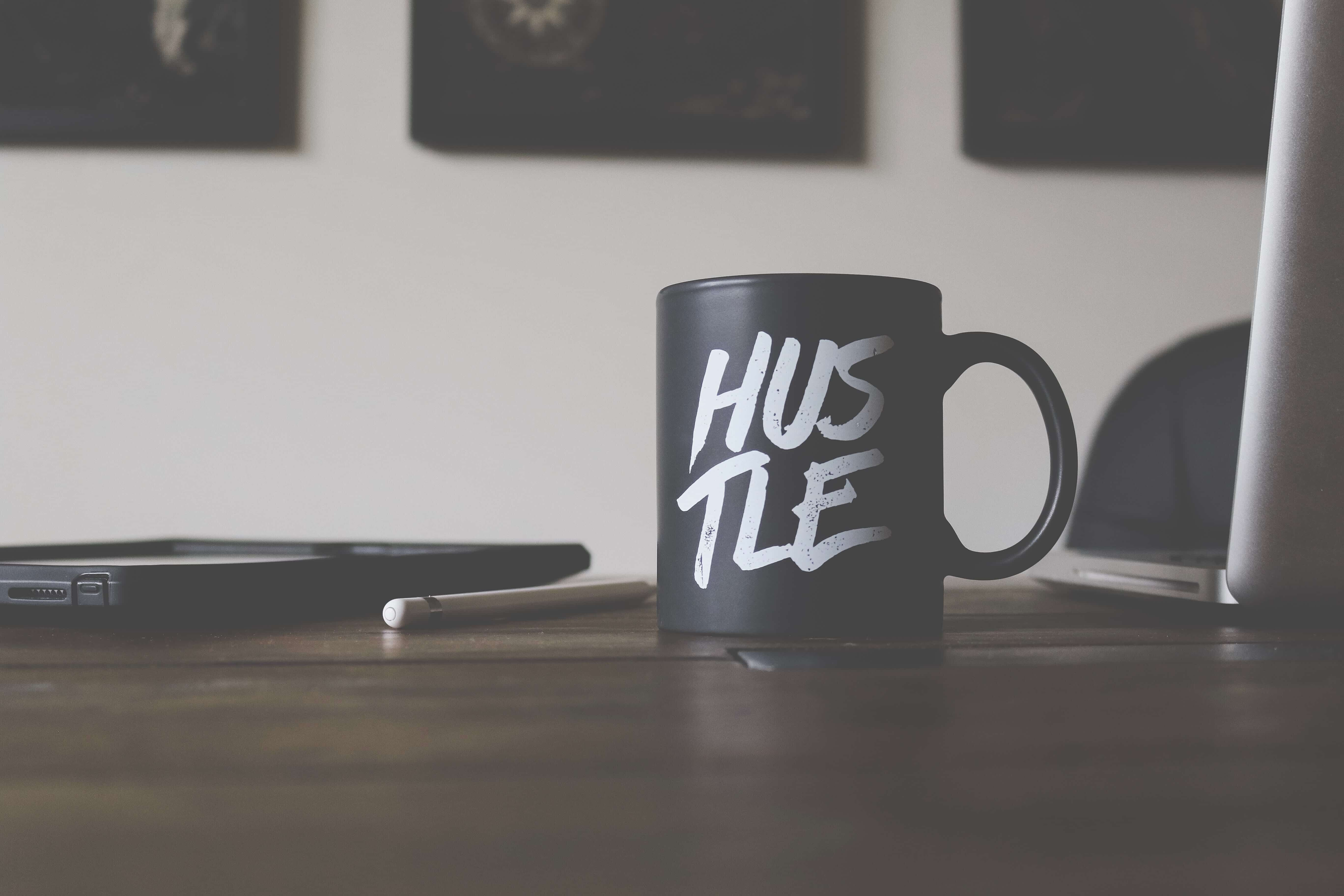"""Black mug with """"Hustle"""" spelled in white letters on table with smartphone, laptop, and pen; image by Lost Co., via Unsplash.com."""