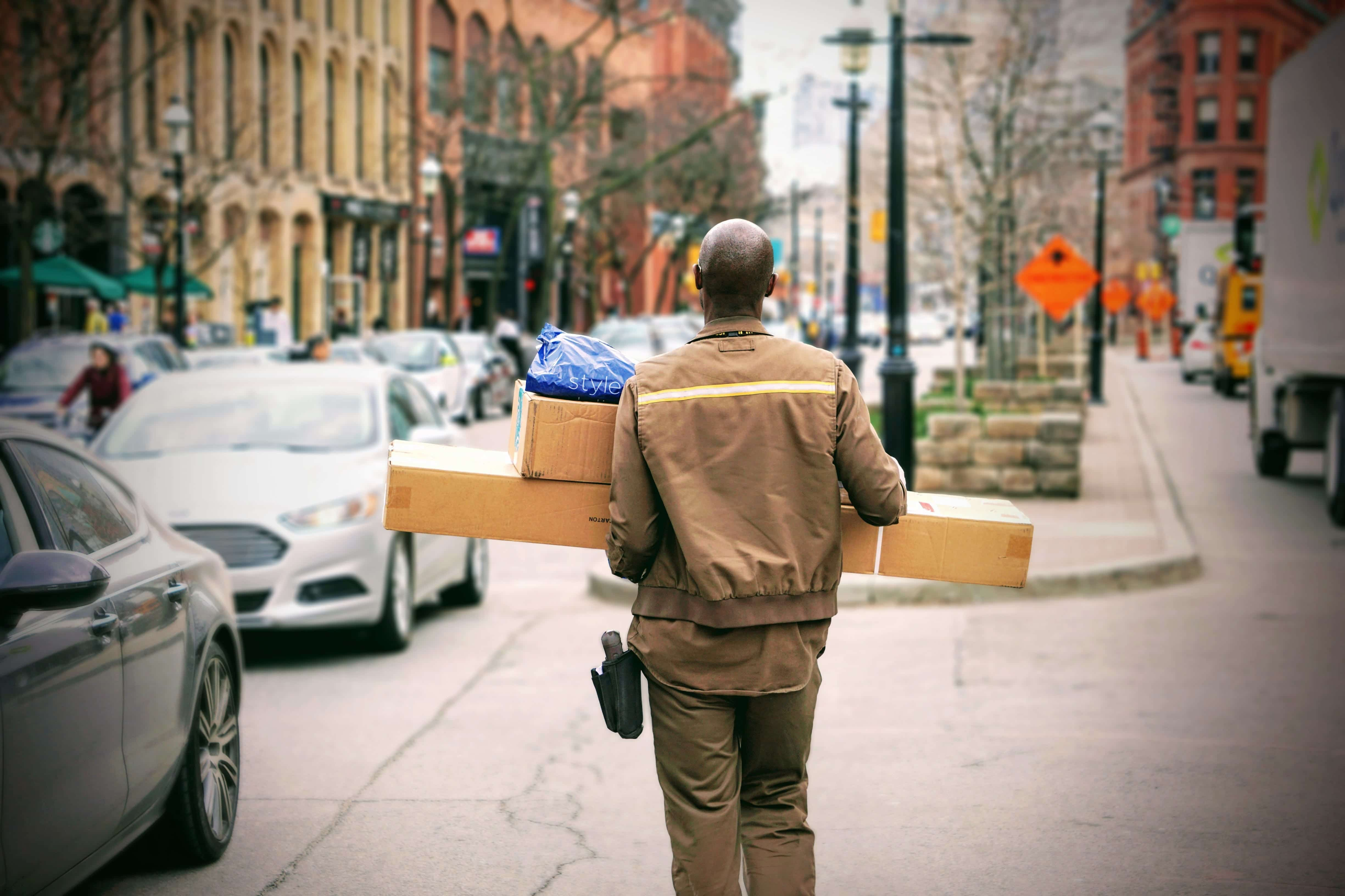 UPS employee in uniform carrying packages; image by Maarten van den Heuvel, via unsplash.com.