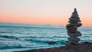 A stack of balanced stones by the water at the beach at sunset; image by Thomas Rey, via Unsplash.com.