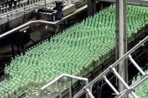 Glass bottles on conveyor belt; image by Waldemar Brandt, via Unsplash.com.