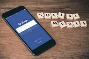 """Smartphone with Facebook login on screen, sitting on table with Scrabble tiles spelling """"Social Media;"""" image by William Ivey, via Unsplash.com."""