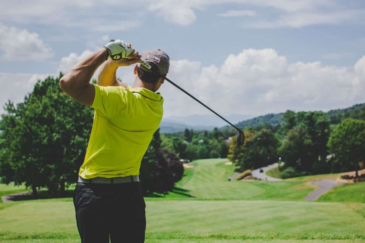 Man in bright yellow shirt finishing golf swing on golf course; image by Court Prather, via Unsplash.com.