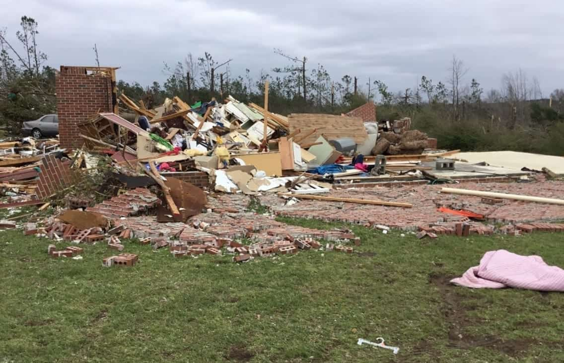 Image of a home leveled by a tornado, surrounded by debris.