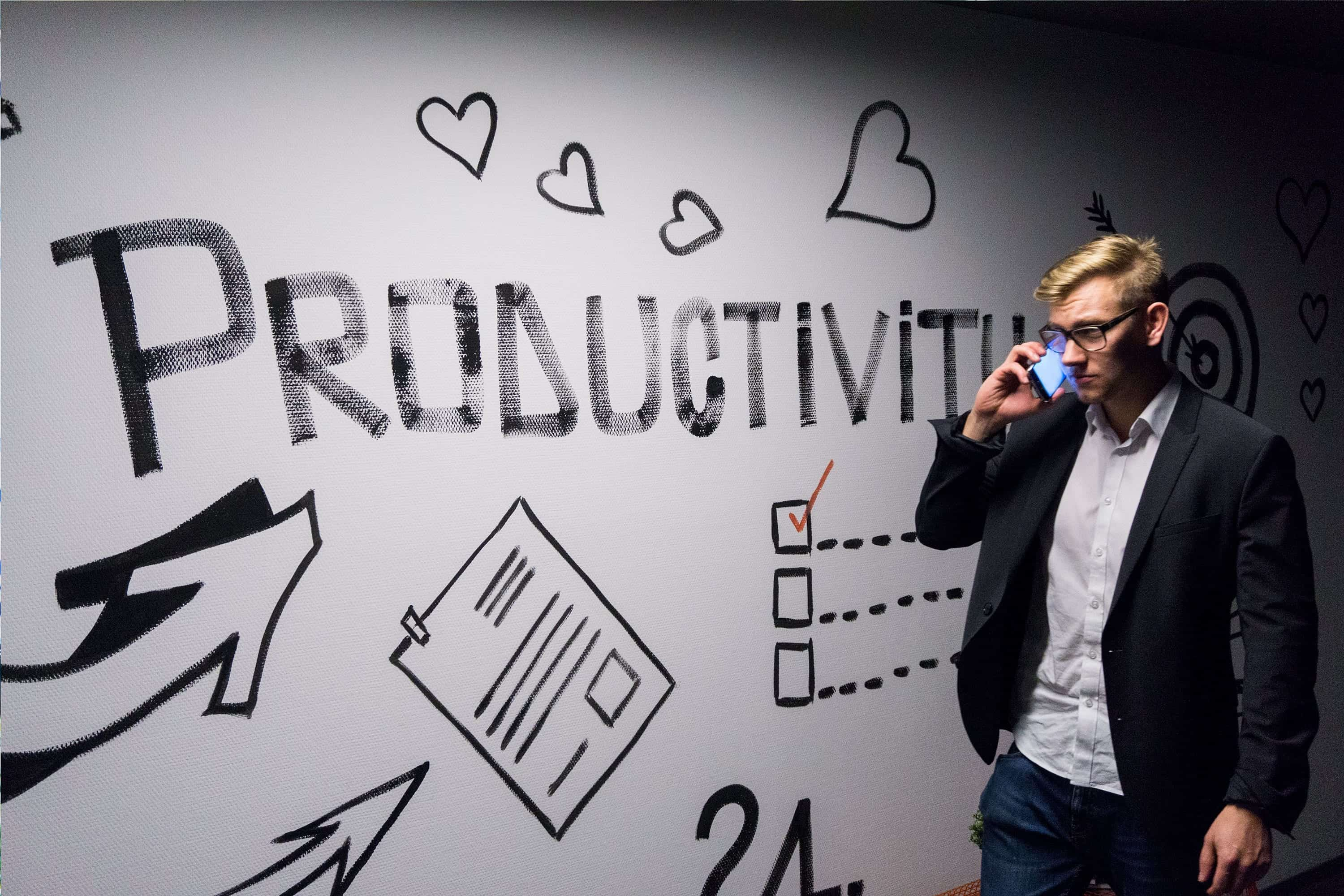 Man holding smartphone looking at whiteboard about productivity; image by Andreas Klassen, via Unsplash.com.