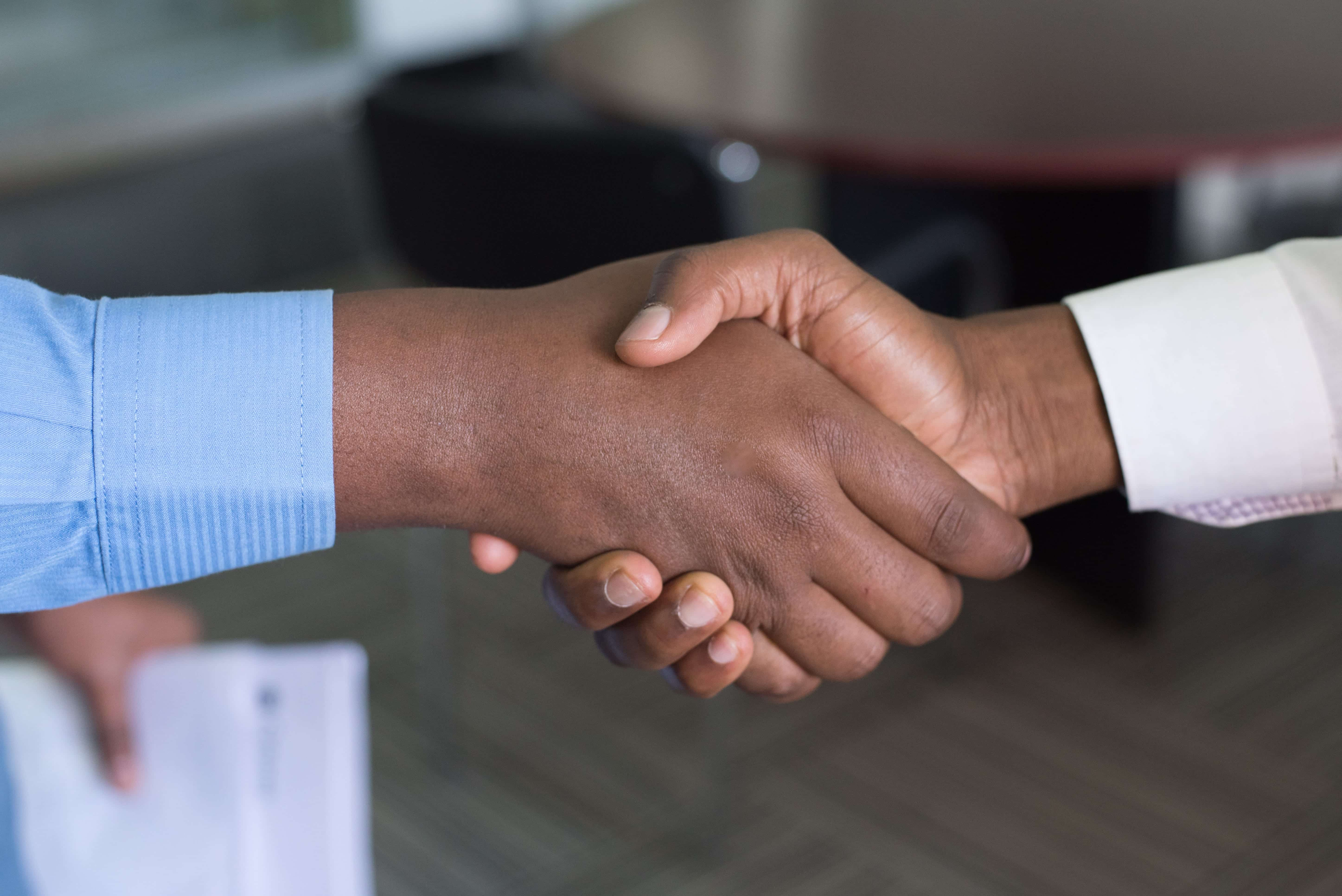 Two men shaking hands; image by Cytonn Photography, via Unsplash.com.