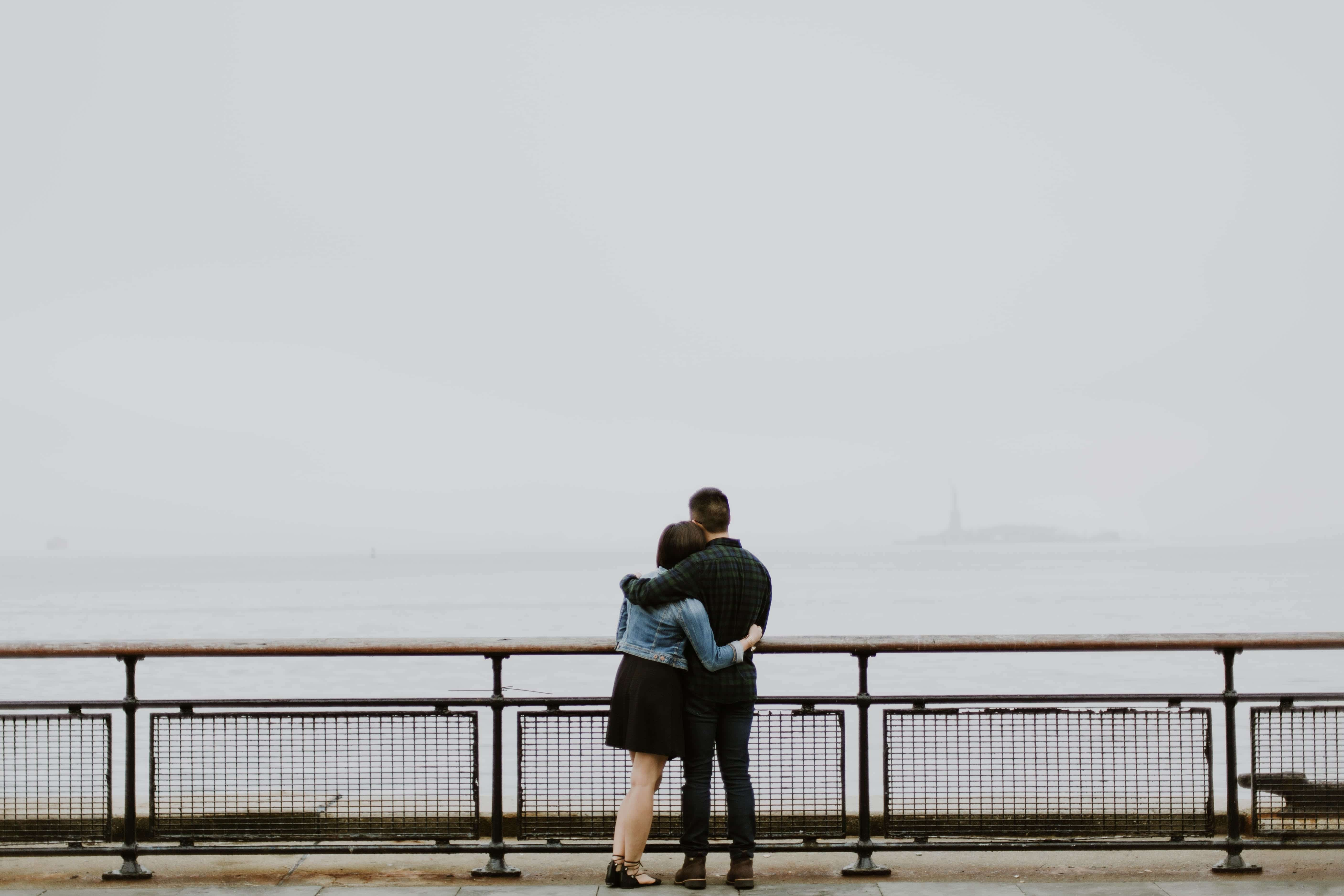 Couple holding each other, standing at railing overlooking water; image by Elizabeth Tsung, via Unsplash.com.