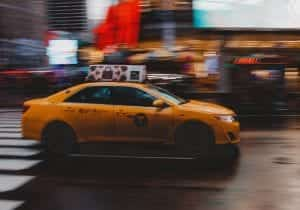 Yellow taxi driving down street, scenery blurred; image by @gehartyler, via Unsplash.com.