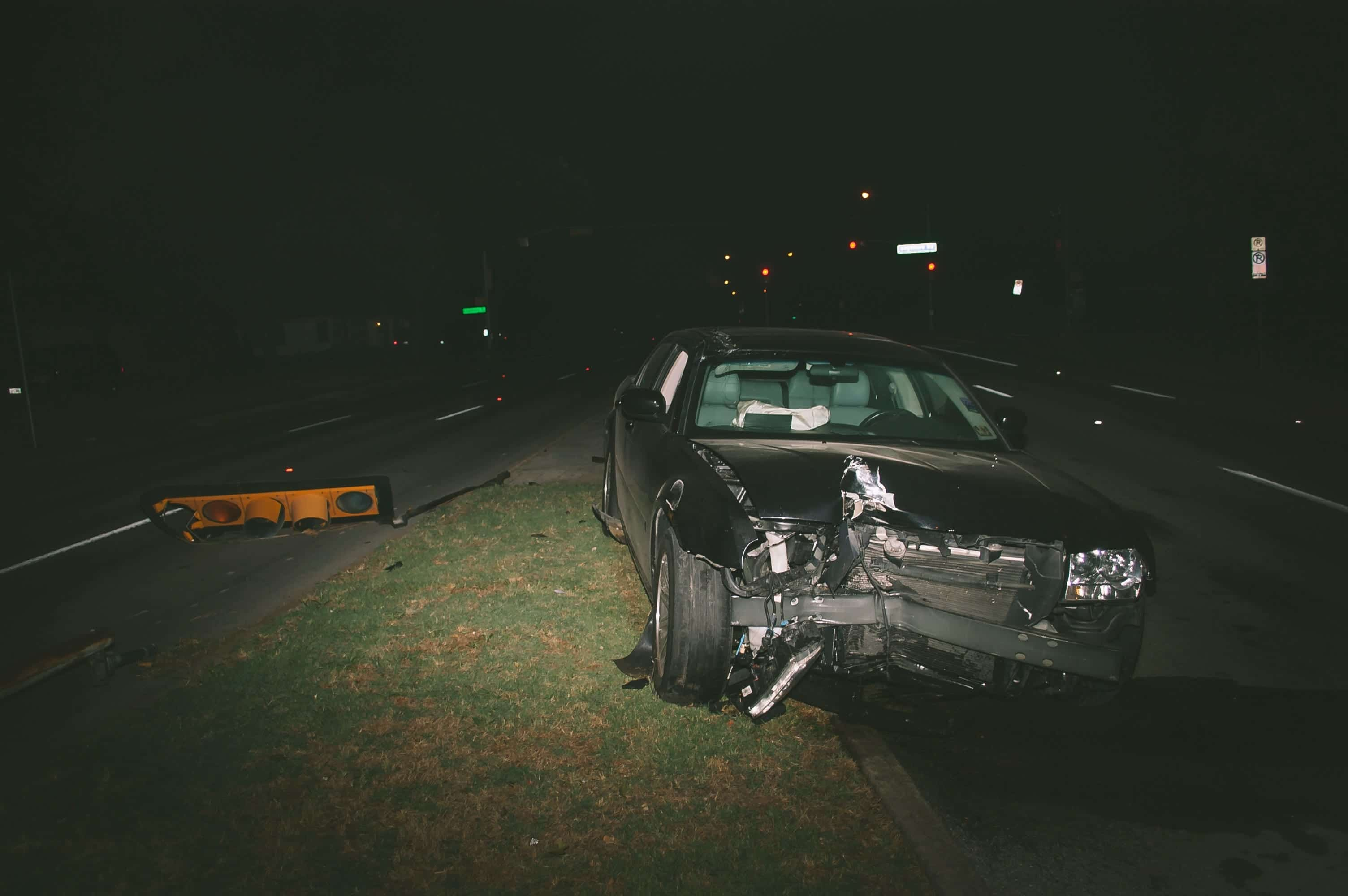 A car with serious front-end damage in the street at night next to a fallen traffic light; image by Matthew T. Rader, via Unsplash.com.