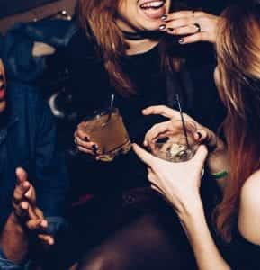 Two women talking while holding drinks; image by Michael Discenza, via Unsplash.com.