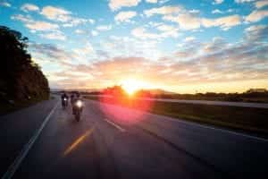 Three motorcyclists riding on an open road at sunset; image by Rafael Lopes de Lima, via Unsplash.com.