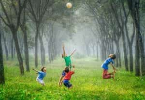 Four boys playing with a ball on a grassy forest path; image by Robert Collins, via Unsplash.com.