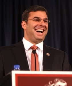 Justin Amash, wearing a dark suit, white shirt, and red tie, stands behind a podium with a wide, laughing smile on his face.