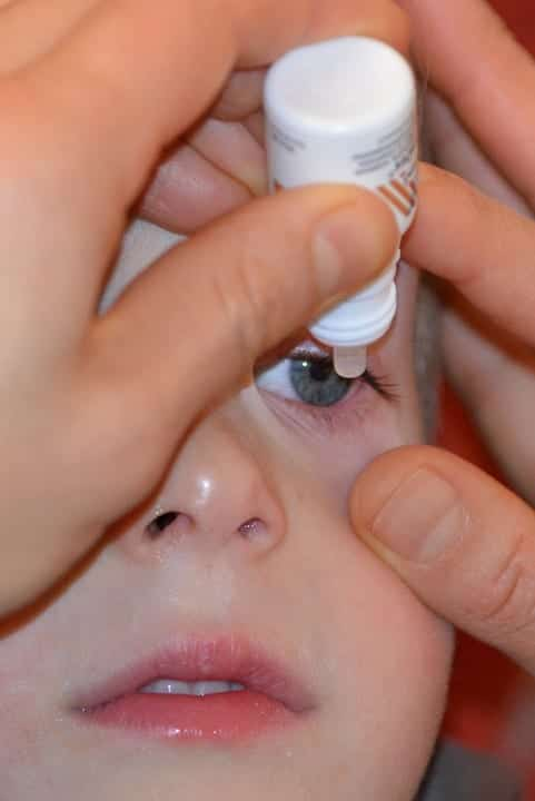 Applying eye drops to a child