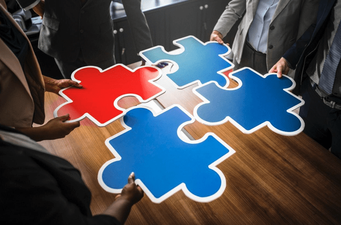 People holding large, multi-colored puzzle pieces over a table, trying to fit them together; image by rawpixels.com, via pexels.com.