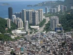 A massive shanty town of makeshift hones and unnamed streets lies against a glittering big city and oceanfront background.