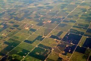 Grid squares of farmland in various shades of green, as seen from above the countryside.