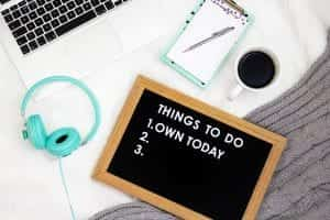 "White desk with computer keyboard, coffee mug, turquoise headphones and clipboard, and a to-do list with ""Own today"" as the number one item. Image by Emma Matthews, via Unsplash.com."