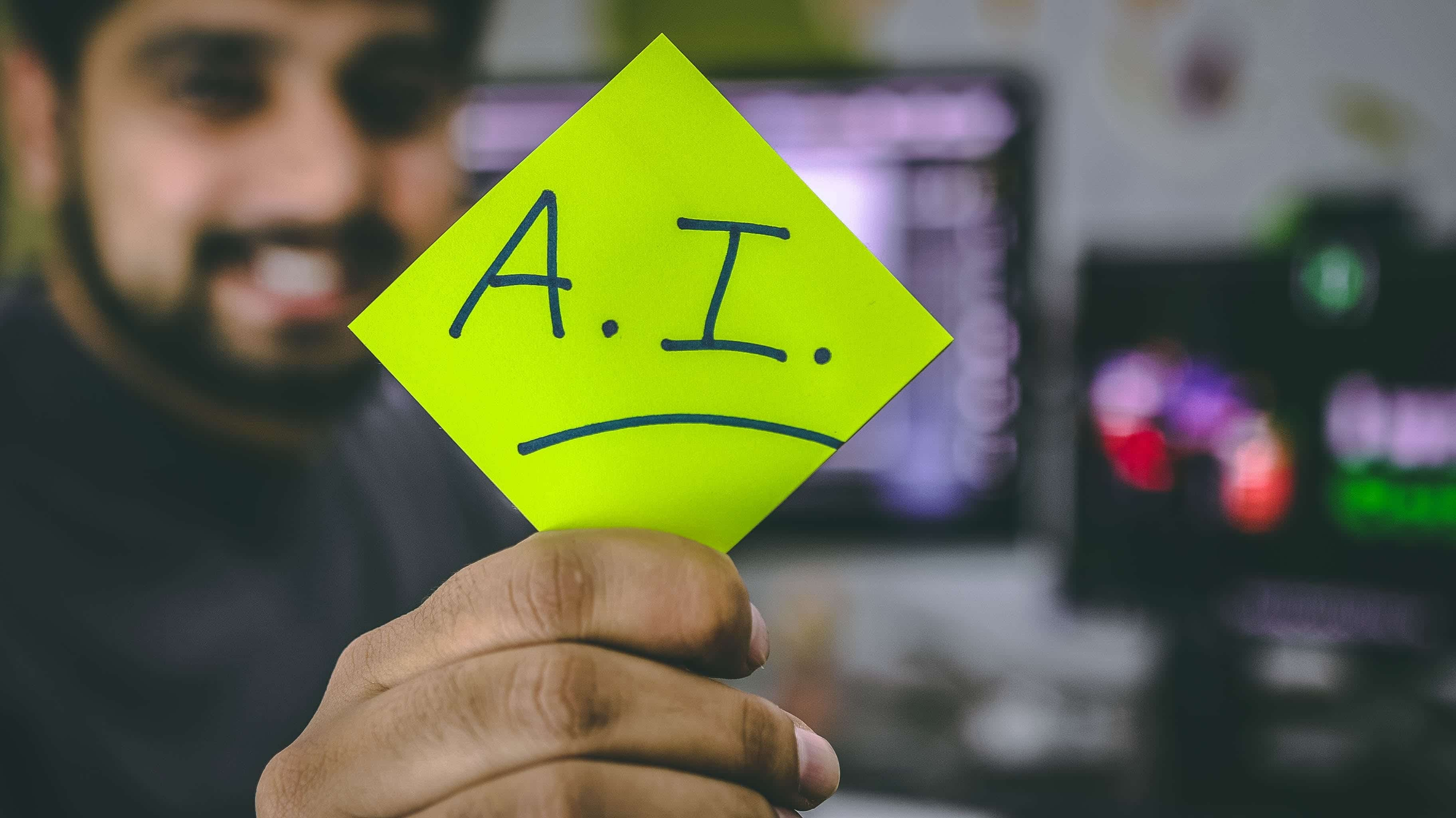 "Man holding green sticky note that says ""A.I."" Image by Hitesh Choudhary, via Unsplash.com."