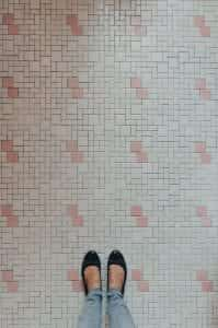 Woman's feet and legs, in black shoes and jeans, on pink and white tile; image by Kelly Sikkema, via Unsplash.com.