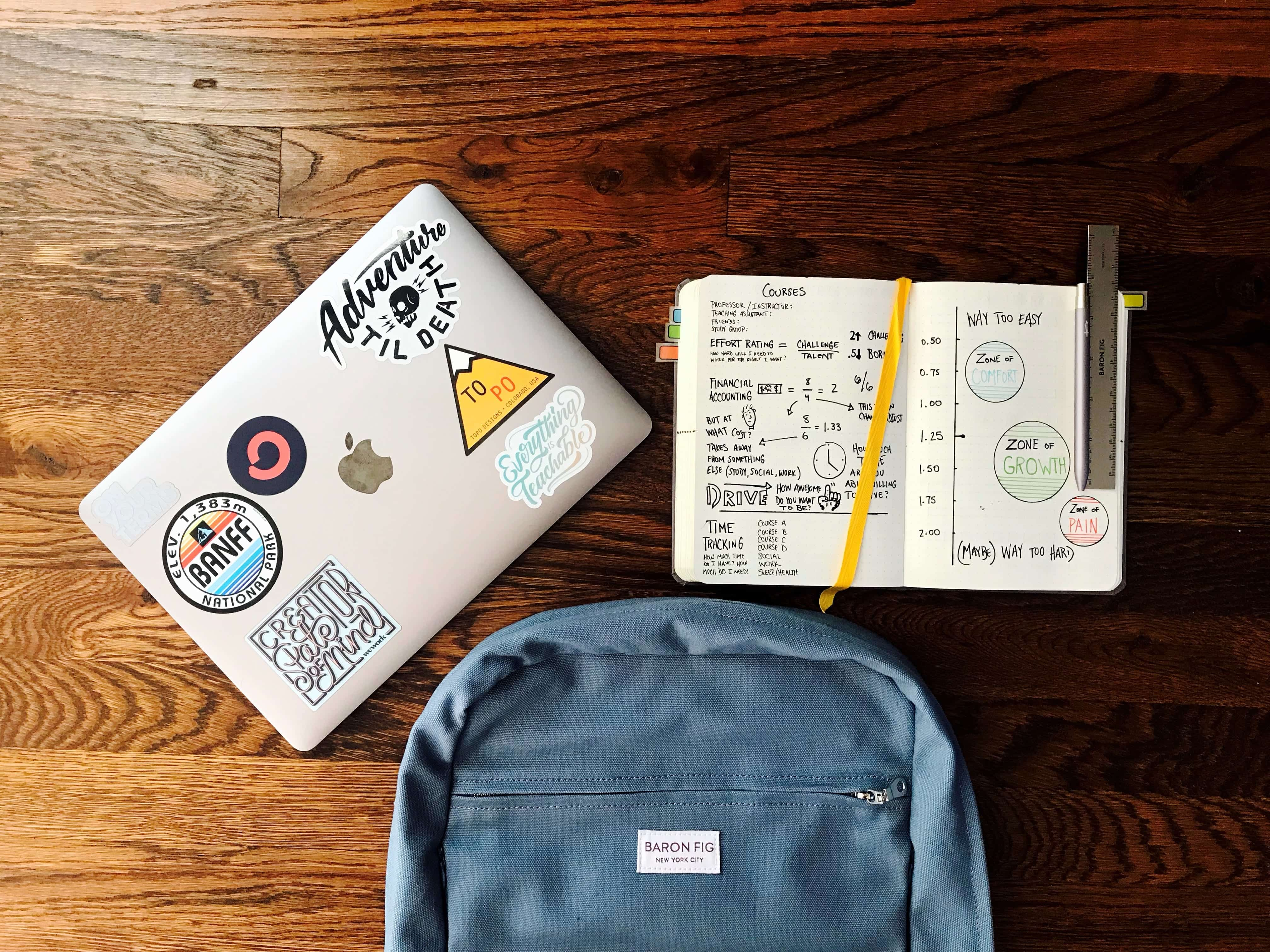 Laptop with stickers on it, blue backpack, and notebook on a brown woodgrain desk; image by Matt Ragland, via Unsplash.com.