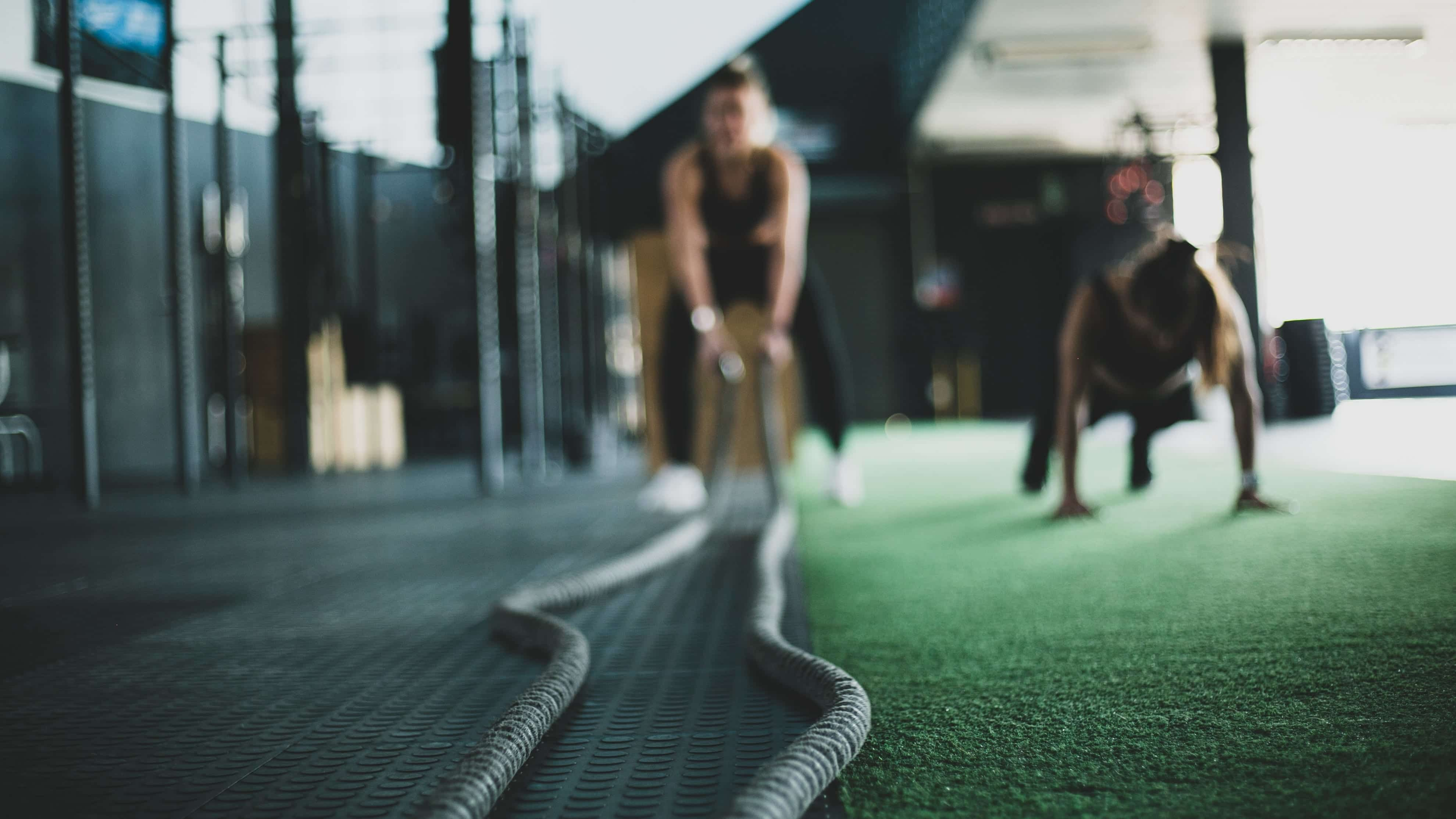 One woman doing push-ups and another using battle ropes at the gym; image by Meghan Holmes, via Unsplash.com.