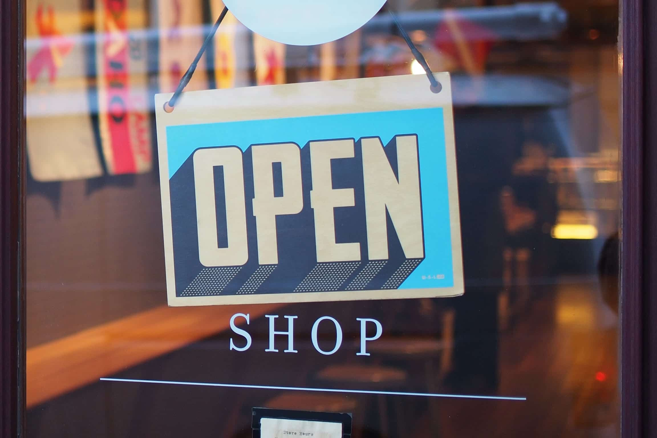 """Grey and blue """"Open"""" sign hanging in shop window; image by Mike Petrucci, via Unsplash.com."""