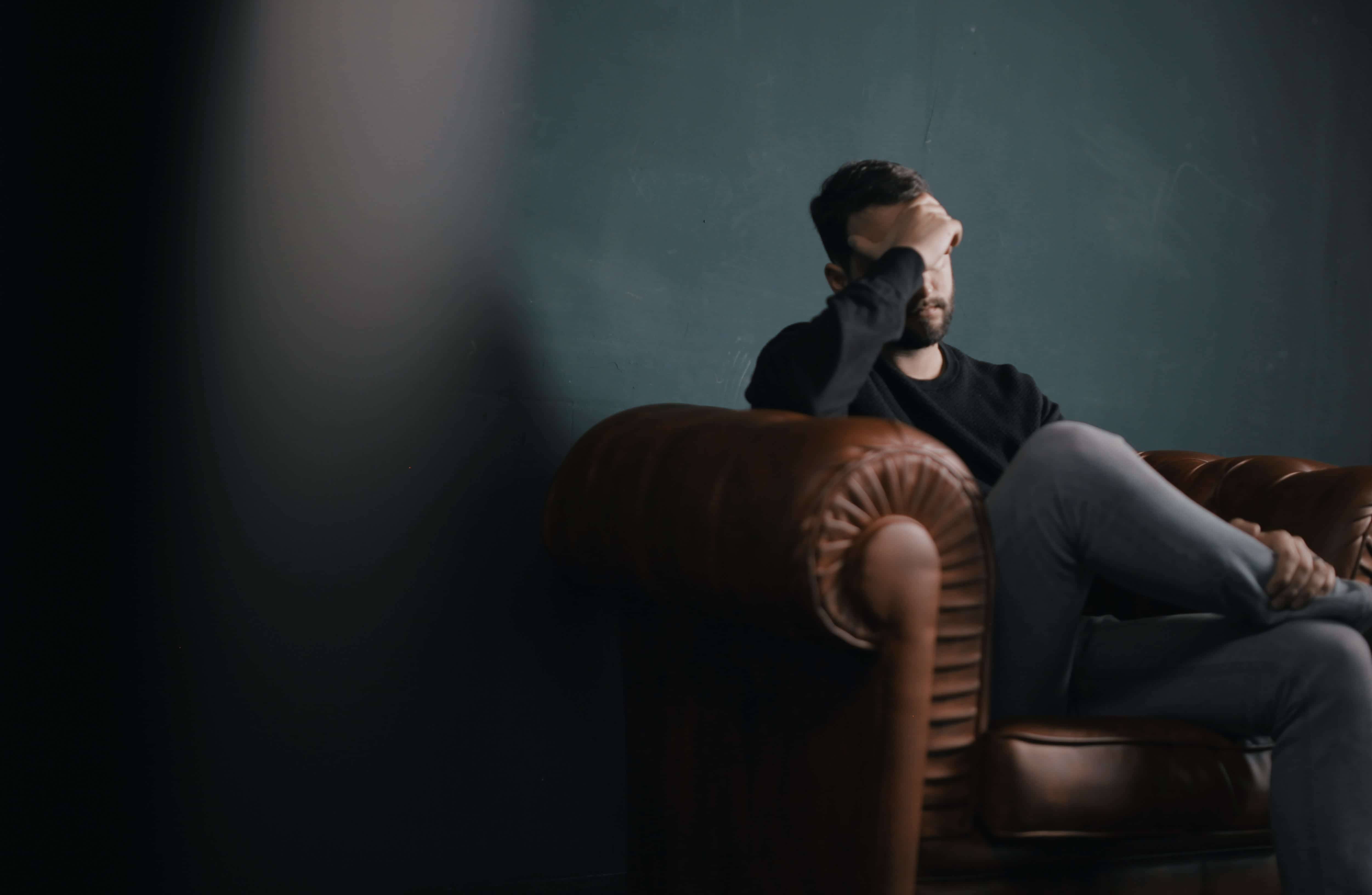 Man sitting on brown leather sofa covering his eyes with one hand; image by Nik Shuliahin, via Unsplash.com.