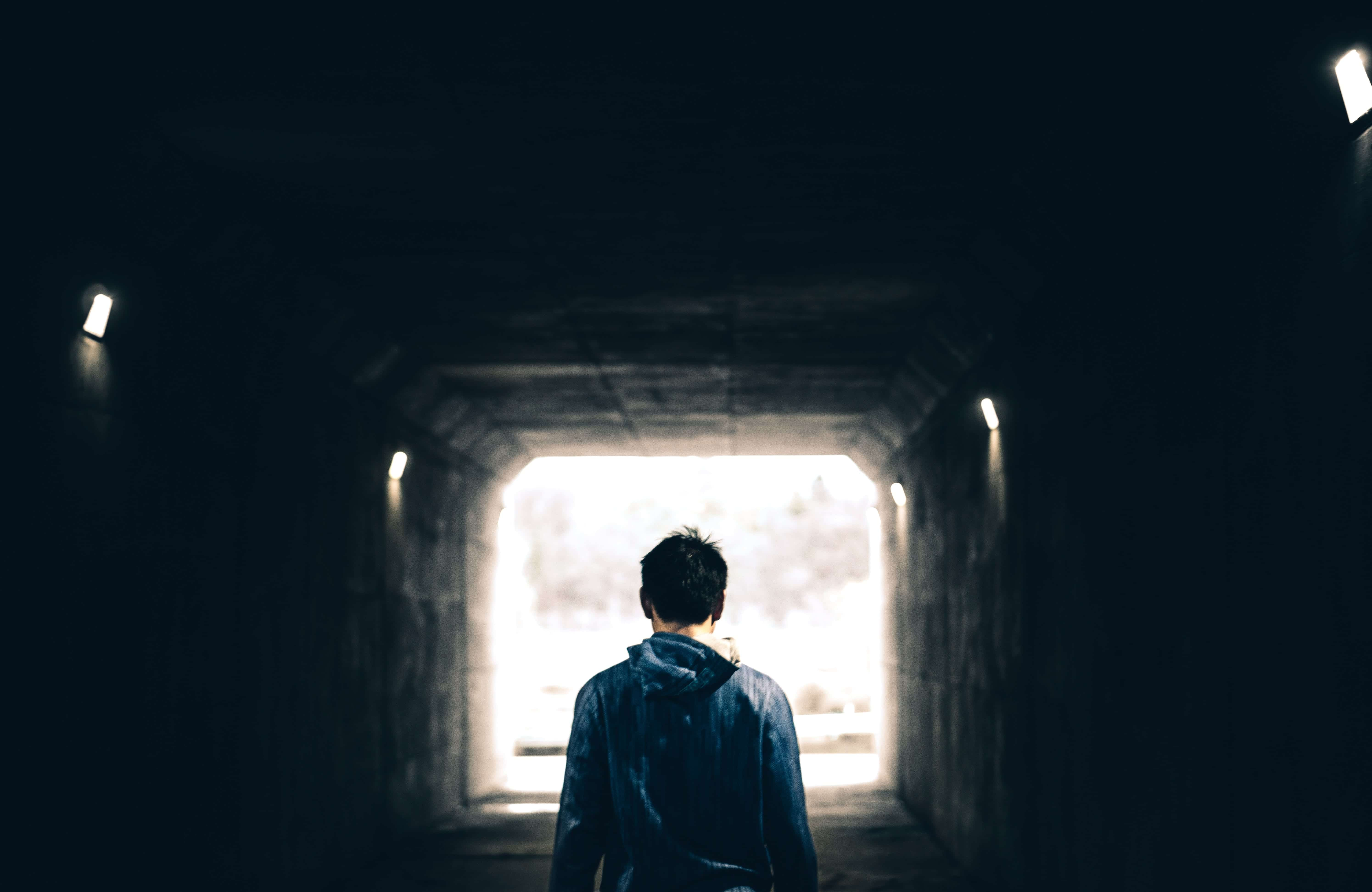 Man walking toward light at the end of a tunnel; image by Warren Wong, via Unsplash.com.