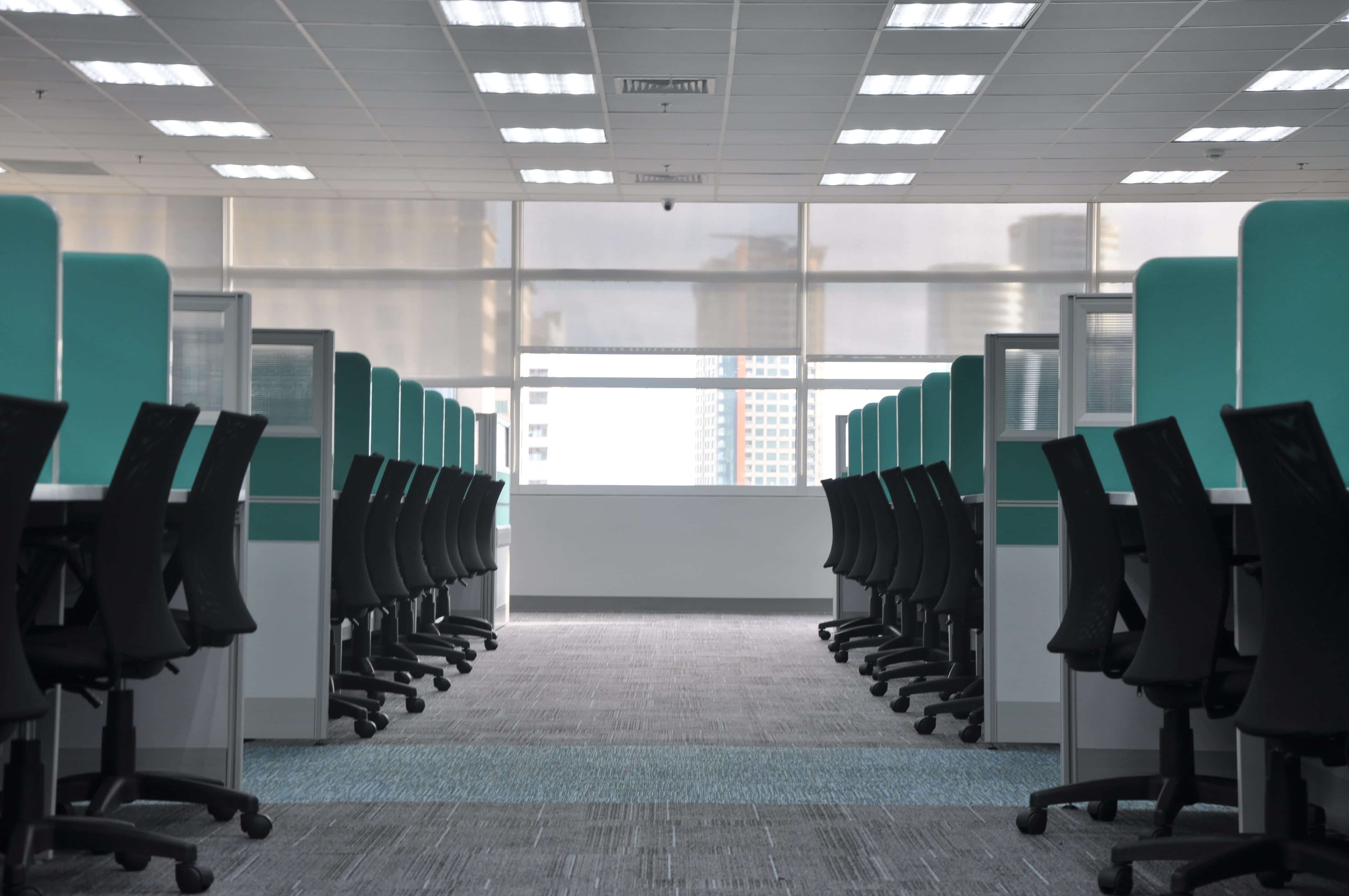 Rows of empty workstations with teal walls and black chairs; image by Kate Sade, via Unsplash.com.