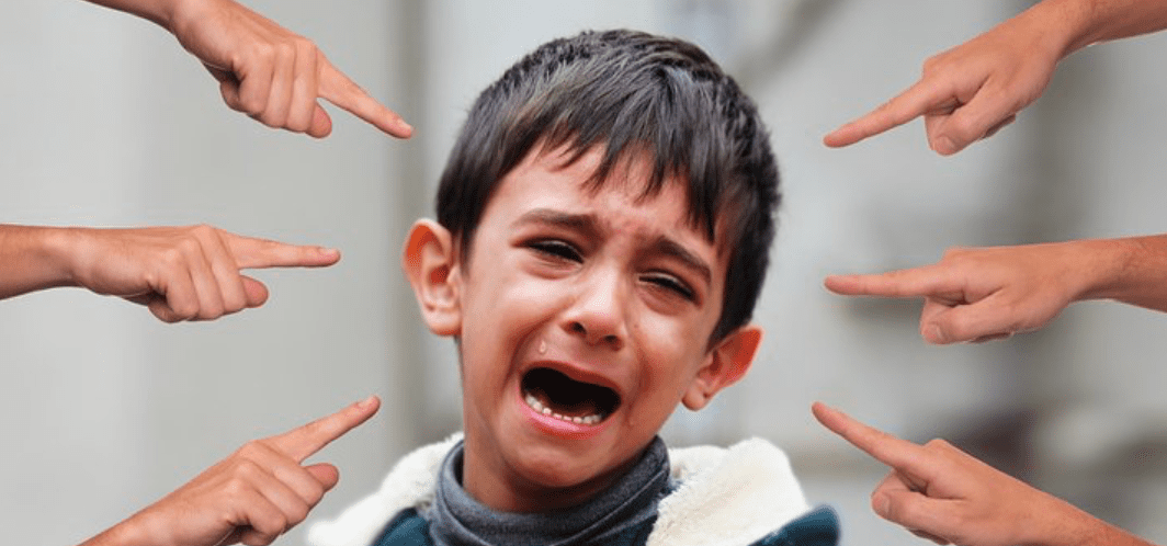 Young boy crying surrounded by multiple hands pointing fingers at him; image by geralt, via Pixabay.com.