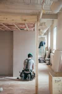 Construction worker kneeling in front of a wall; image by Charles, via Unsplash.com.