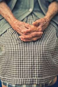 Elderly woman with hands folded in her lap; image by Cristian Newman, via Unsplash.com.