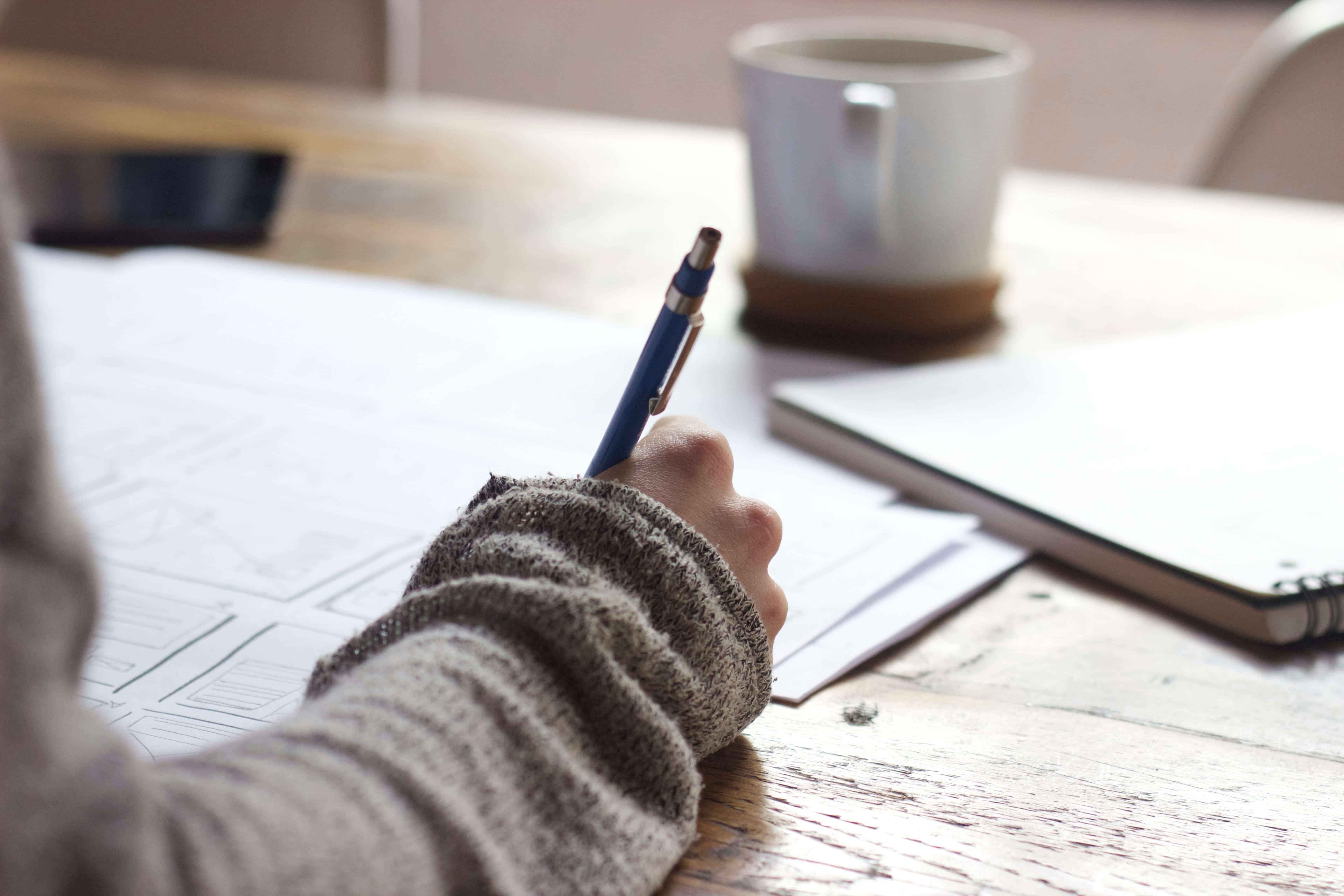 Person in grey sweater with notebook, pen, and papers, with mug in background; image by Green Chameleon, via Unsplash.com.