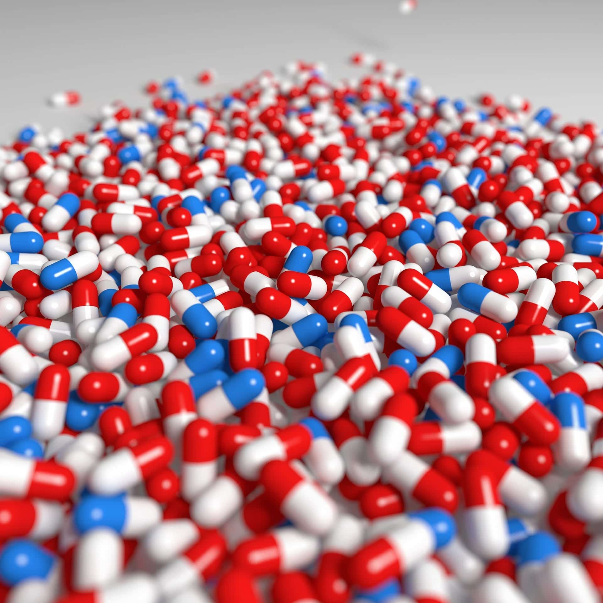Red/white and blue/white capsules; image by mmmCCC, via Pixabay.com.
