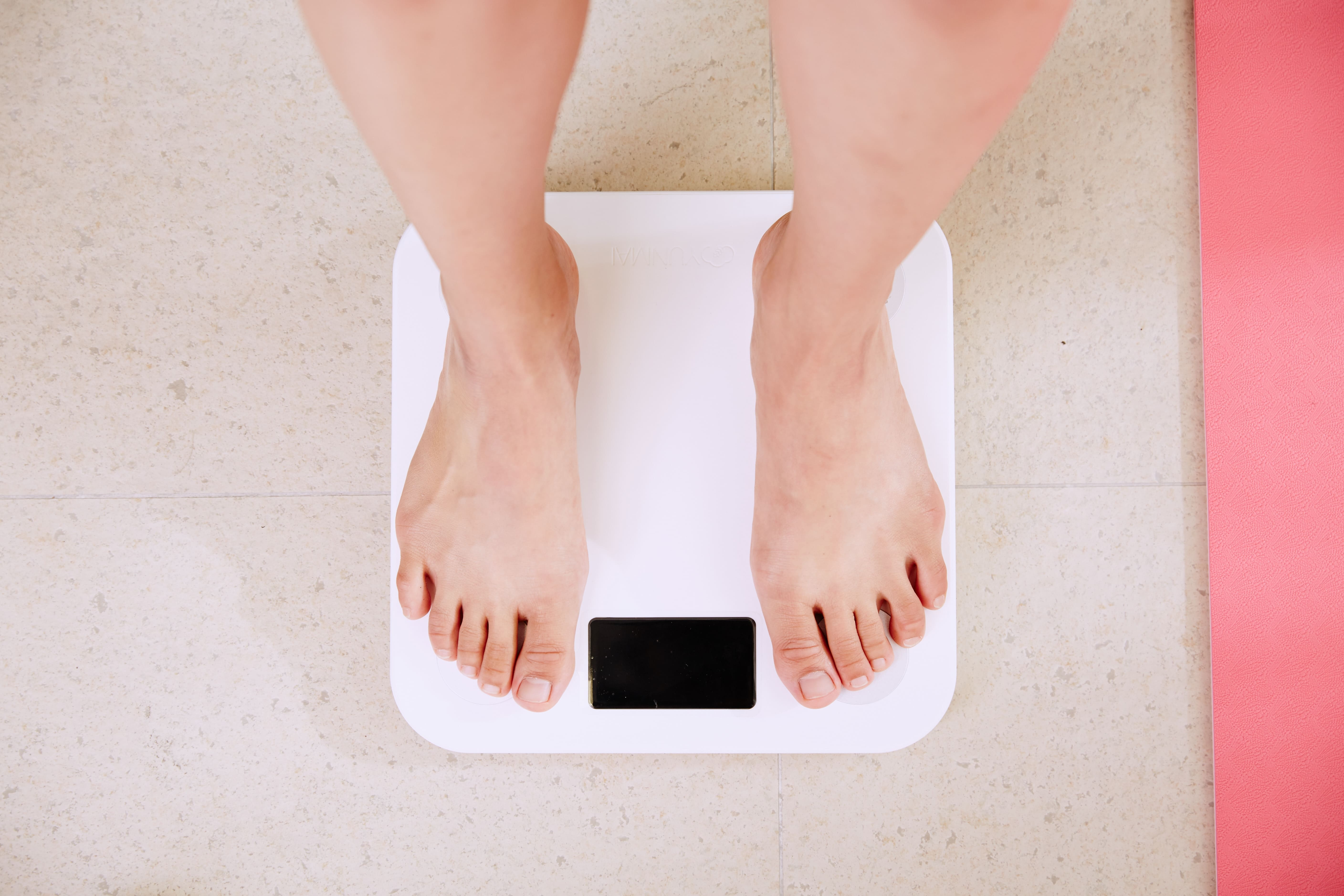 Person standing on white scales; image by I Yunmai, via Unsplash.com.