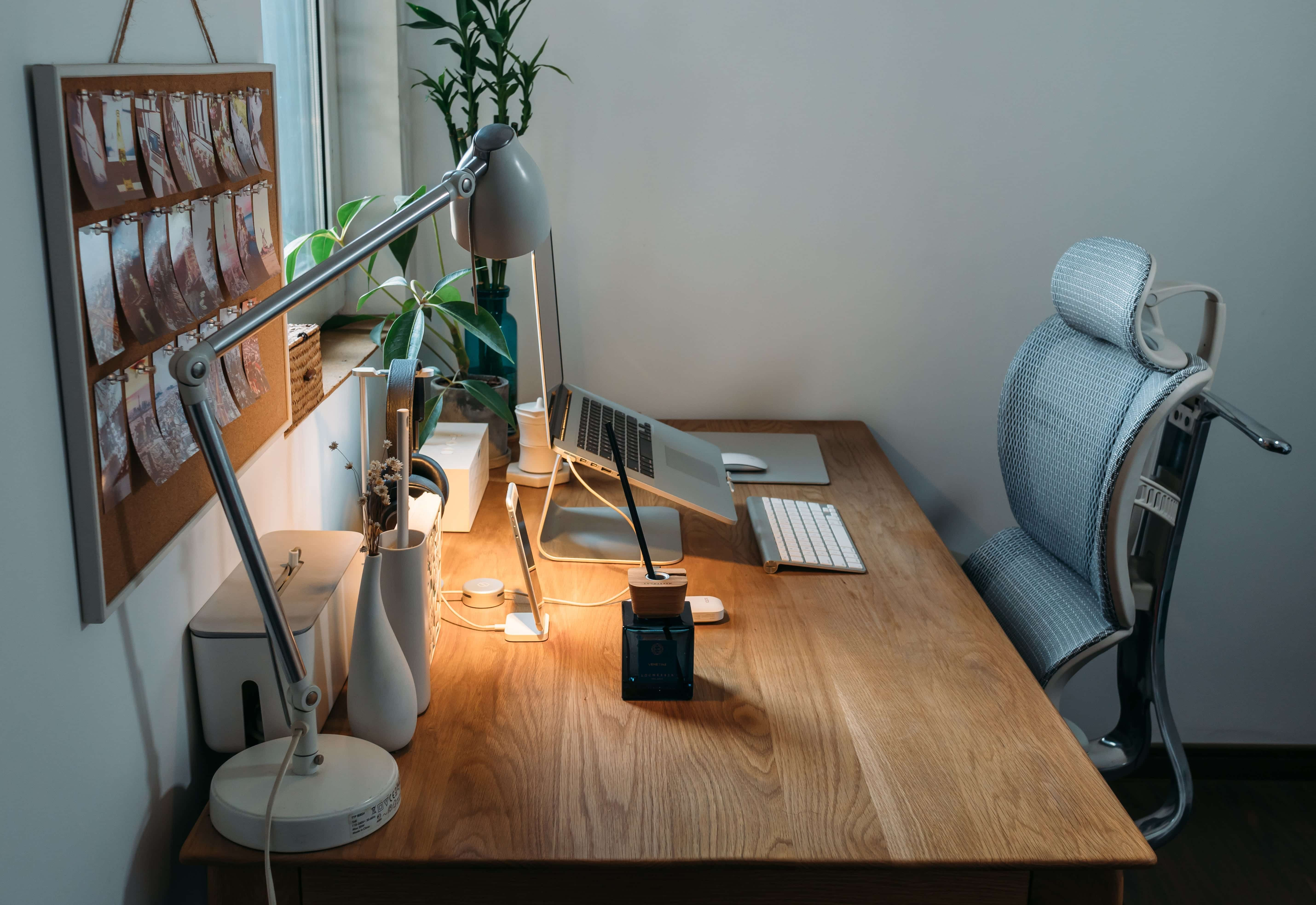 Desk with computer, lamp, and personal effects; image by Samule Sun, via Unsplash.com.