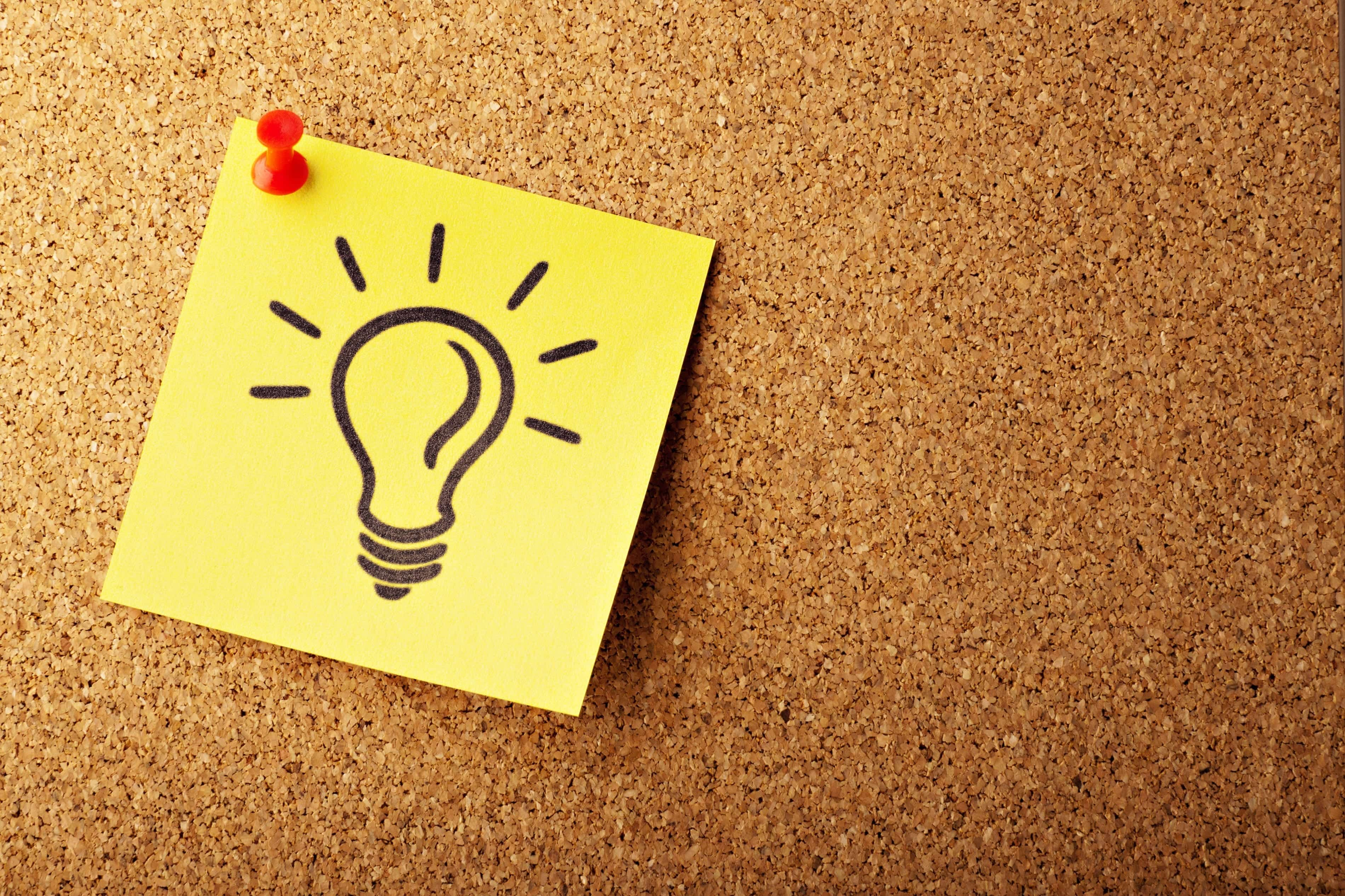 Yellow sticky note with a light bulb drawn on it tacked to a cork board; image by AbsolutVision, via Unsplash.com.