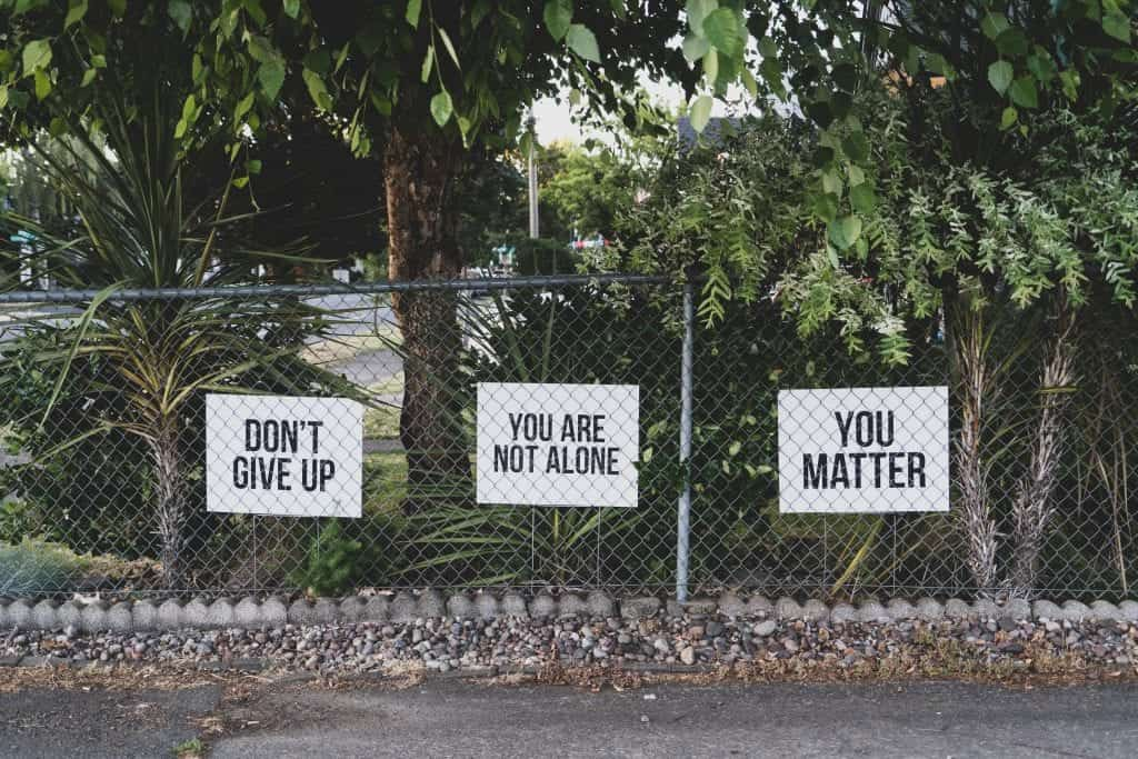 """Three signs on a chain link fence, reading (in order) """"Don't Give Up,"""" """"You Are Not Alone,"""" and """"You Matter."""" Image by Dan Meyers, via Unsplash.com."""