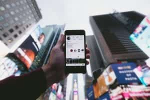 Man holding a smartphone toward the sky with tall buildings in the background; image by Jakob Owens, via Unsplash.com.