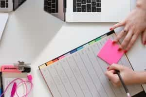 Woman holding pencil and pink sticky note next to laptop and planner; image by Marten Bjork, via Unsplash.com.