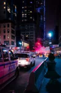 Two police SUVs on a New York City street at night; image by Matteo Monica, via Unsplash.com.