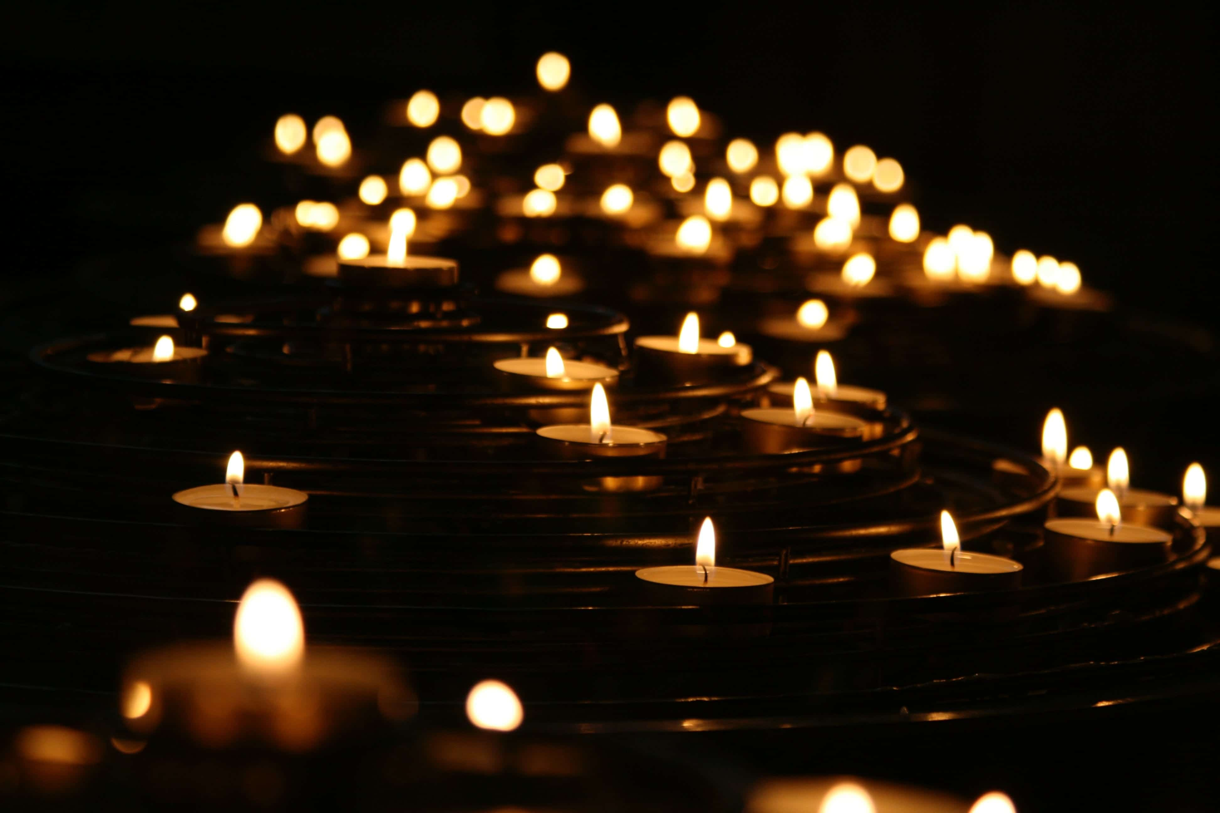 Low-angle photo of lighted candles; image by Mike Labrum, via Unsplash.com.